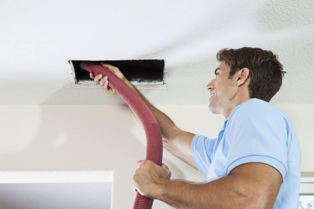 man cleaning ducts