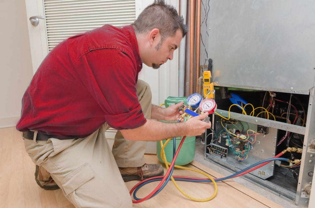 technician tuning up furnace